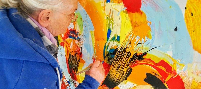 Etelka Kovacs-Koller malt details an einem großformatigen Gemälde